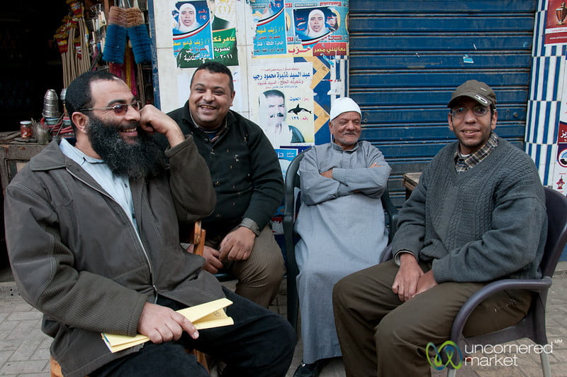Group of Egyptian men chatting on the sidewalk in Alexandria, Egypt.