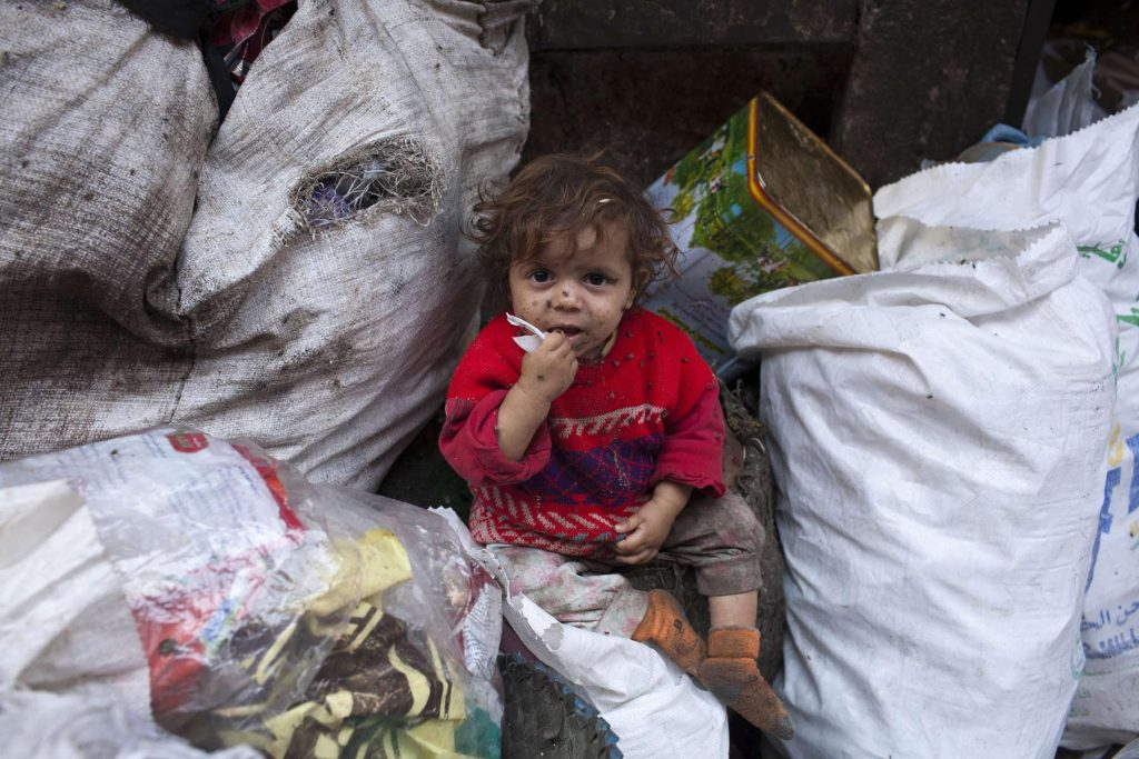 A child sitting among trash in the Zabaleen district of Moqattam.