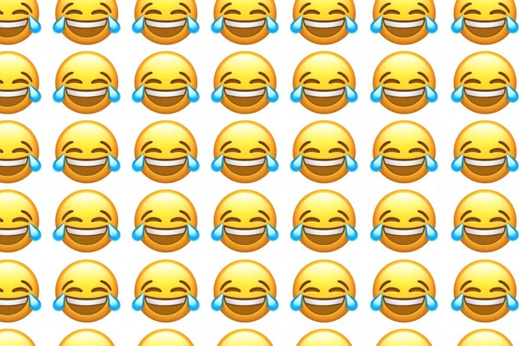 Wall of smiley faces with laugh cry emojis, to show how people laugh online in Arabic, Chinese, Spanish, Korean, Farsi, Hebrew and other languages