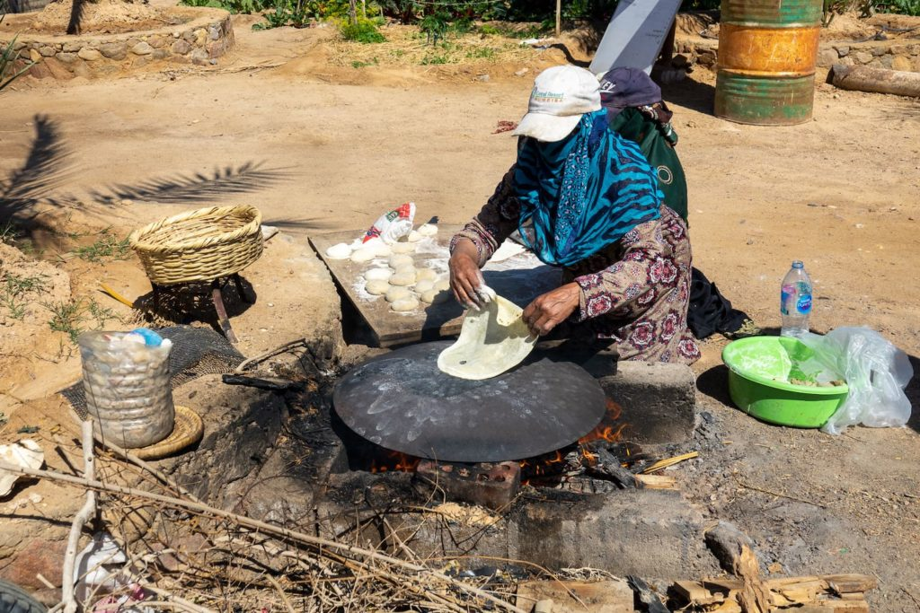 A Bedouin woman making flatbreads on an iron fire stove. In South Sinai, Egypt.