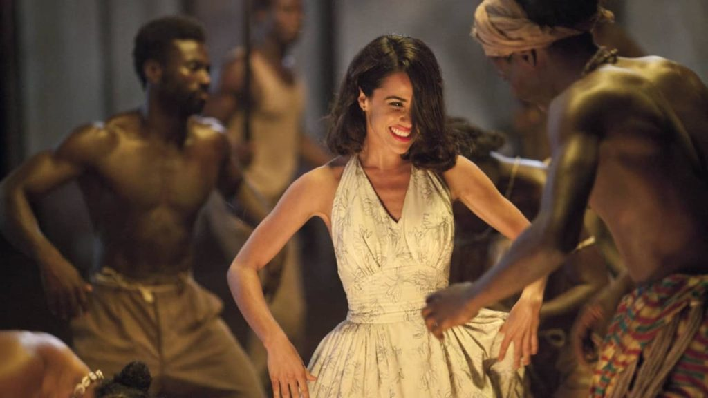 Screenshot from Palmeras en la nieve with a woman dancing with a group of people